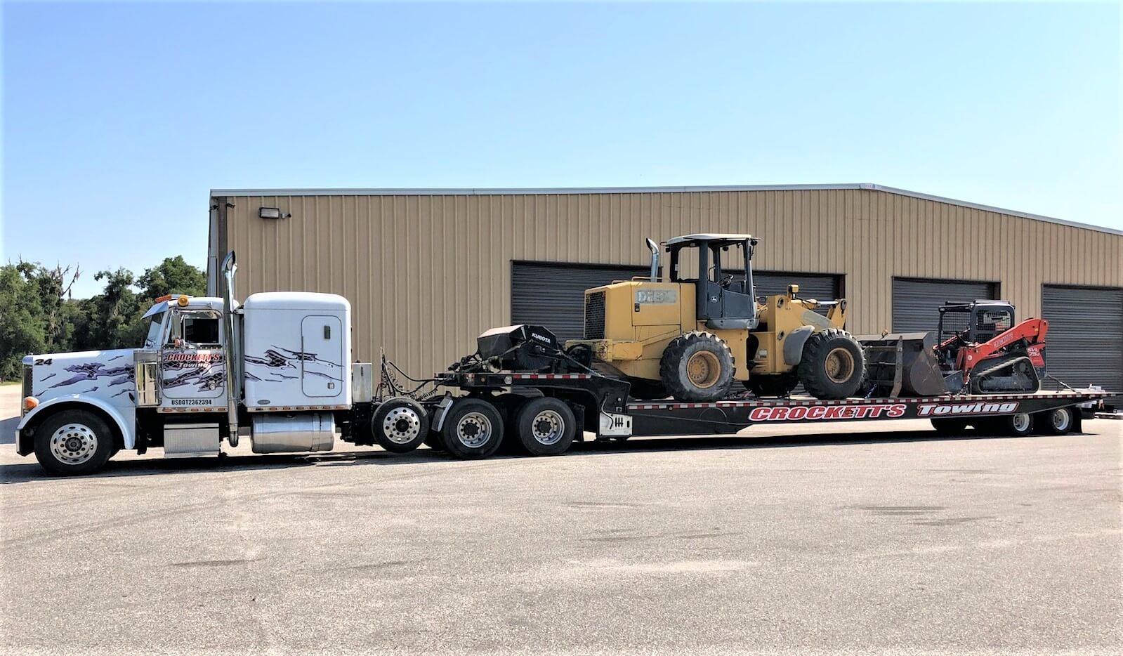Professional truck transporting construction equipment